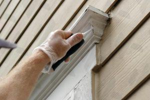 painter-doing-exterior-paint-repair-in-spokane-adding-caulk-to-white-trim