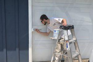 spokane-painter-painting-white-trim-next-to-white-garage
